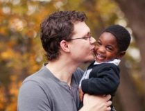 Father kissing toddler son